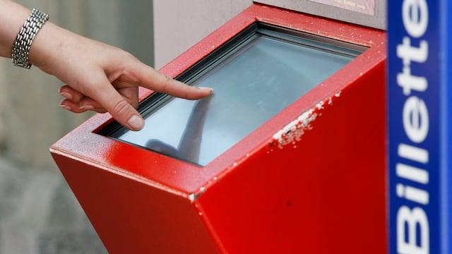Eine Frauenhand bedient einen SBB-Billett-Automaten