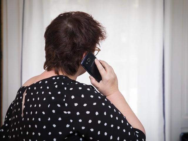 Eine Frau mit schwarzer Bluse mit weissen Punkten telefoniert mit ihrem Handy.