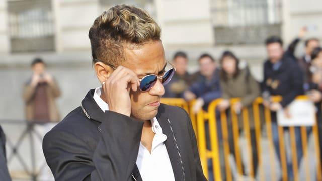 Neymar spielt an seiner Sonnenbrille.