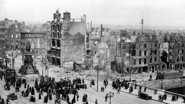 Schwarzweiss Aufnahme, Menschen im Vordergrund, im Hintergrund zerstörte Gebäude