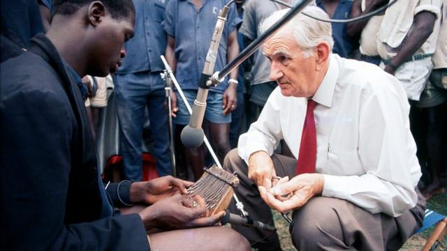 Mann sitzt mit Mikrofon vor einem Afrikaner, der ein spezielles Instrument spielt.