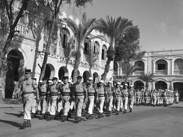 Soldaten Marschieren in Formation auf einem mit Palmen gesäumten Exerzierplatz.