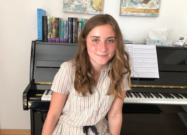 Mädchen sitzt vor dem Klavier