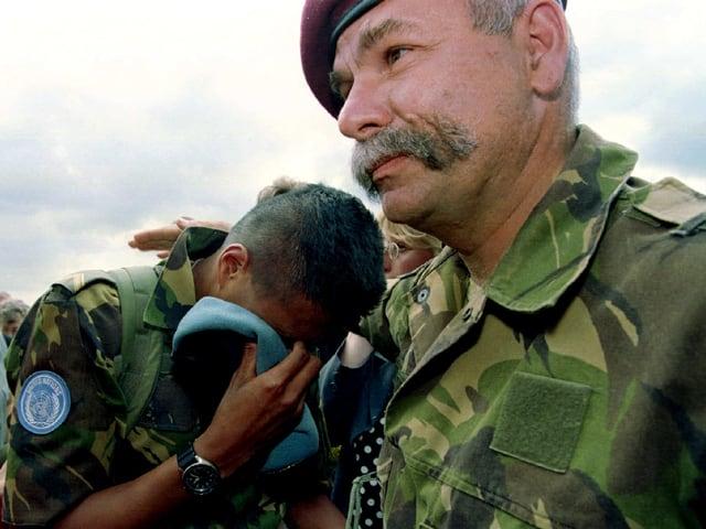 Ein Uno-Blauhelm weint an der Schulter eines anderen.