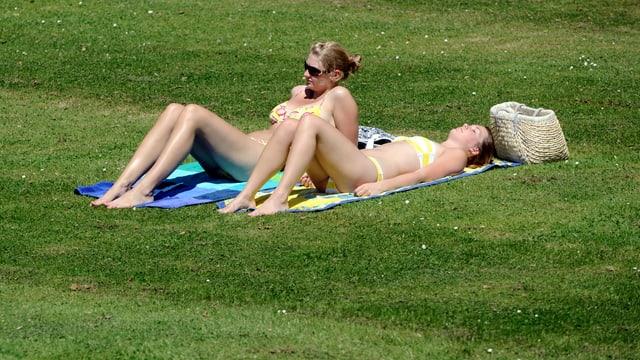 Zwei Frauen im Bikini sonnen sich auf der Wiese (Symbolbild)