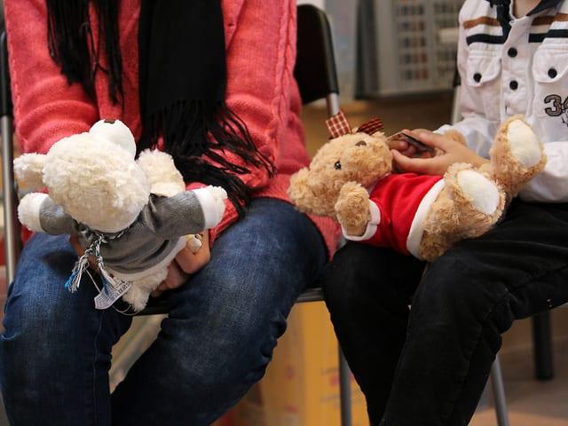 Zwei Kinder haben die JRZ-Teddybären auf ihrem Schoss.