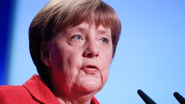 Angela Merkel in rotem Kleid in Grossaunfahme vor Mikrofonen