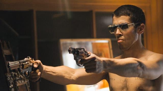 Ein Mann mit Sonnebrille und nacktem Oberkörper hält in beiden Händen eine Waffe.