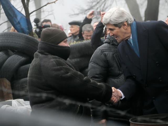 US-Aussenminister Kerry schüttelt in Kiew die Hand einer Demonstrantin.