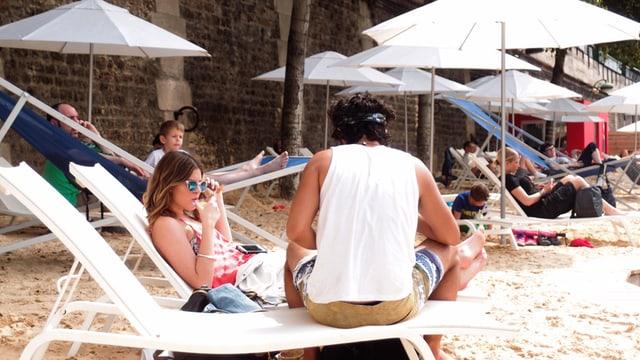 Ein Paar sitzt auf Liegestühlen am Strand.
