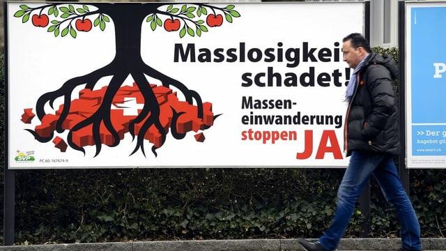 """Plakat der Befürworter der SVP-Volksinitiative """"gegen Masseneinwanderung"""", davor geht ein Mann vorbei. Aufgenommen in Zürich."""