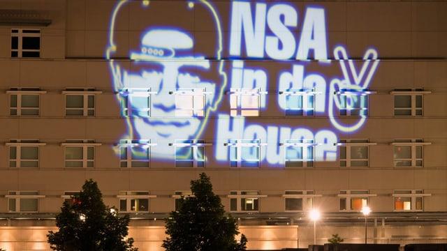 """Zu sehen ist eine Projektion eines Künstlers, auf der steht """"NSA in da House"""". Sie wurde an die amerikanische Botschaft in Berlin projiziert."""