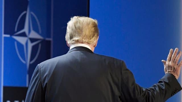 Trump von hinten vor Nato-Logo