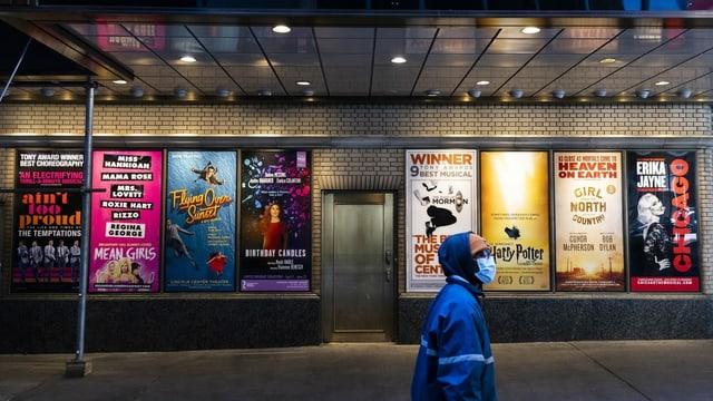 Verschiedene Poster von Musical- und Theater-Shows in New York, vorne ein Mann mit Maske