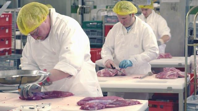 Männer mit gelben Hauben und weissen Schürzen schneiden Fleisch zurecht.