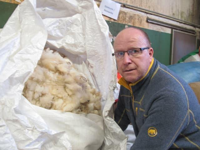 Niklaus Sägesser vor einem Sack mit weisser Schafwolle