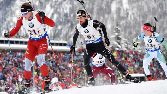 Drei Biathleten laufen sich auf Skiern nach. Das Gewehr haben sie auf dem Rücken angeschnallt.