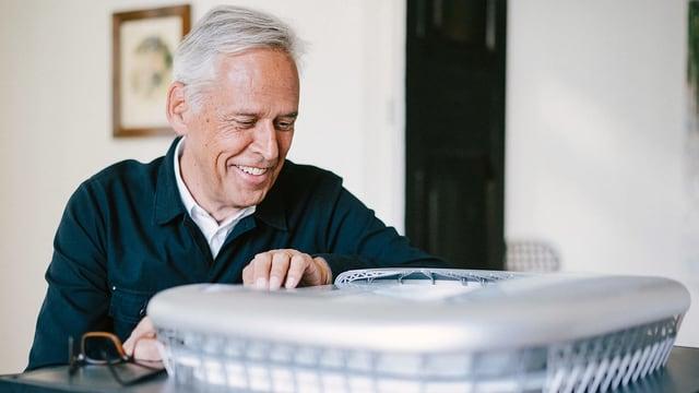 Ein Mann mit grauen Haaren betrachtet ein Modell eines Fussballstadions.