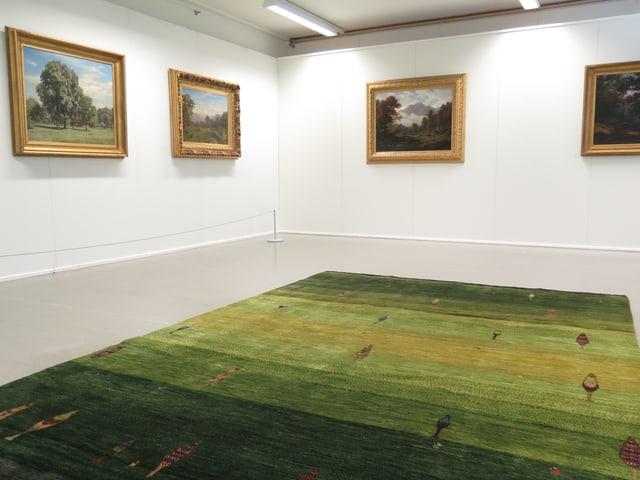 Grüner Teppich im Vordergrund, an den Wänden Gemälde mit Bäumen