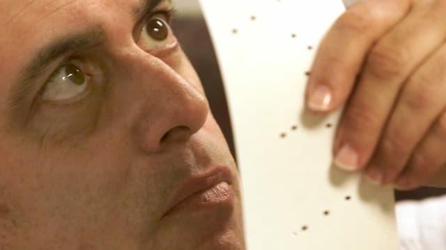 Ein Mann untersucht eine Lochkarte.