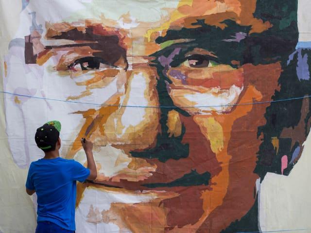 Ein junger Mann malt ein Porträt des verstorbenen Erzbischofs Oscar Romero
