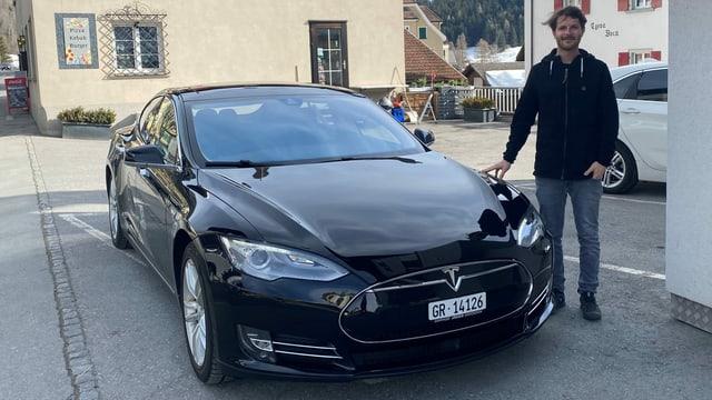 Roberto Guetg davant ses affar d'immobiglias a Savognin cun ses auto electric.