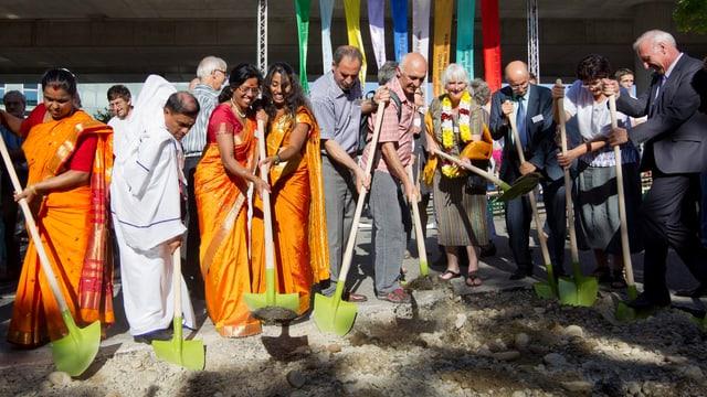 In einer Reihe stehen Frauen in Saris und Männer in geistlichen Kutten. Alle beginnen mit einer Schaufel zu graben.