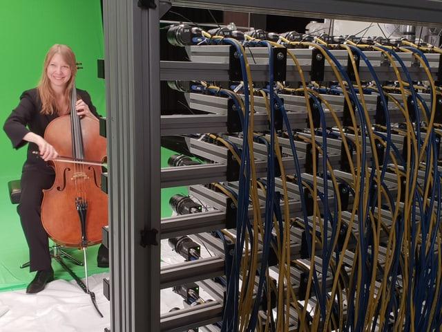 Die Cellistin Cellistin Isabell sitzt vor einem grünen Tuch auf einem Stuhl, vor ihr das Lichtfeld-Rig mit 64 kleinen Kameralinsen.