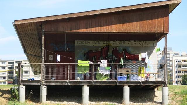 Eine Baracke auf Betonpfeilern, unter dem Dach ist Wäsche aufgehängt.