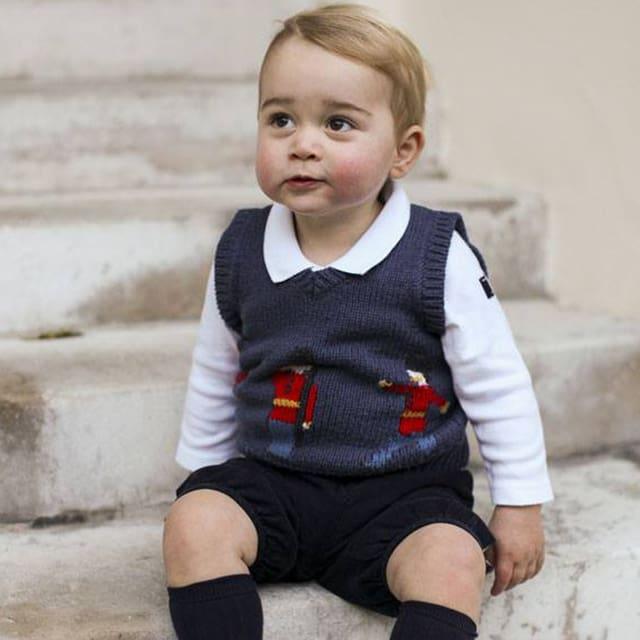Baby George in kurzen Hosen auf einer Steintreppe sitzend.
