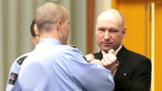 Dem Attentäter Anders Behring Breivik werden im Gerichtssaal im norwegischen Skien von einem Sicherheitsbeamten die Handfesseln abgenommen.