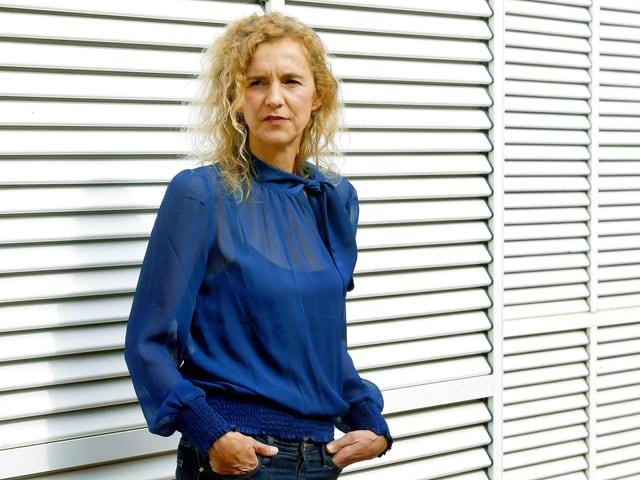 Eine blonde Frau mit blauer Bluse steht vor weissen geschlossenen Rolläden.
