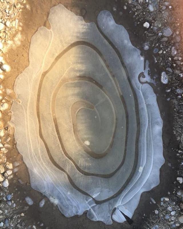 Eine Eispfütze durchzogen mit einer etwas dünkleren Spirale.