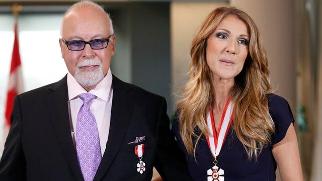 Mann in schwarzem Anzug und Glatze sowie Céline Dion posieren für die Kamera.