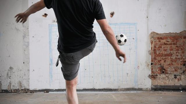 Ein junger Mann kickt einen Fussball in Richtung einer Wand, auf die mit blauer Kreide ein Tor gezeichnet ist.