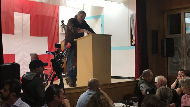 Freysinger auf einer Bühne, hinter ihm eine grosse Schweizerfahne.
