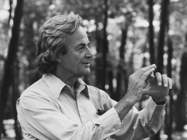 Schwarz-weiss-Porträt von Richard Feynman im Wald.