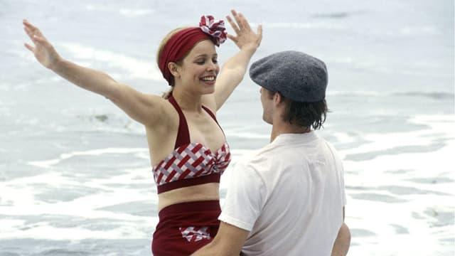 Eine junge Frau und ein Mann, am Strand herumtollend.