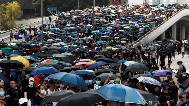 Demonstranten mit Regenschirmen marschieren durch die Strassen Hongkongs.