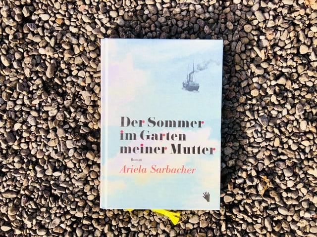 «Der Sommer im Garten meiner Mutter» von Ariela Sarbacher liegt auf einem Kiesboden