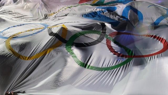 Numerus umans èn cuverts d'ina bandiera olimpica