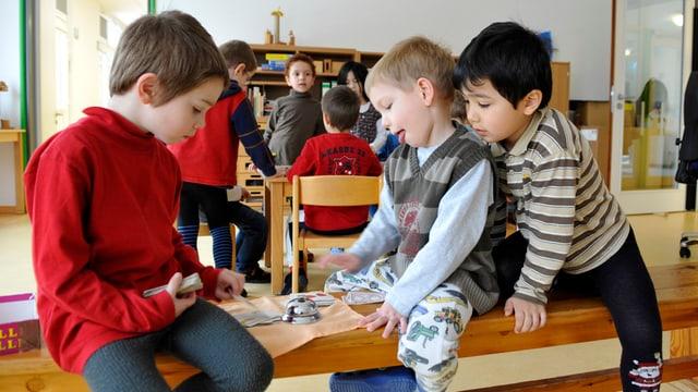 Kinder spielen auf einer Bank.