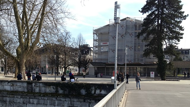 Blick auf den Kreuzackerpark, auf der Mauer am Fluss sitzen unbekannte dunkle Gestalten.