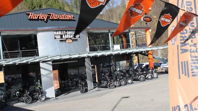 Der harley Laden in Densbüren - Aussenaufnahme. Im Vordergrund sind Harley-Flaggen zu sehen.