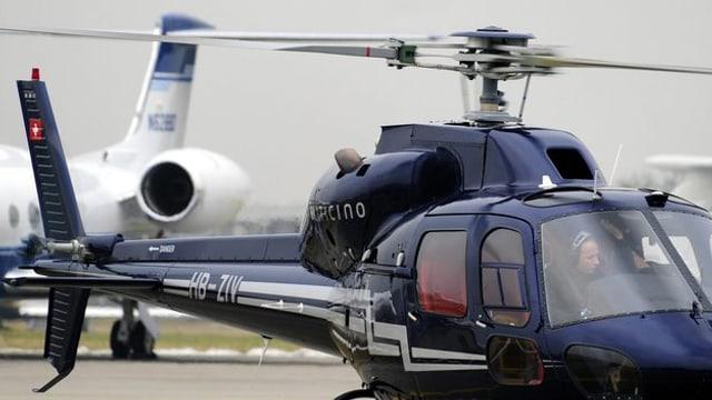 Ein Helikopter neben einem Flugzeug am Boden