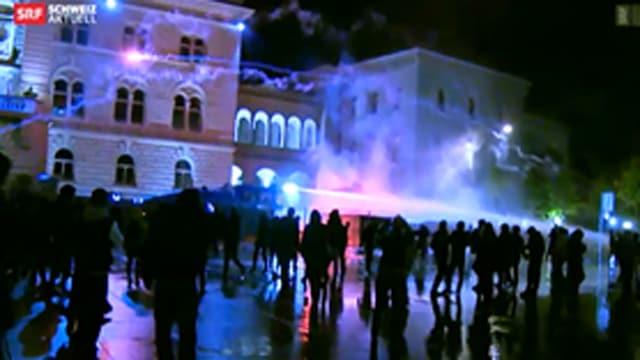 Vermummte Personen vor dem Bundeshaus bei Nacht, Feuerwerk fliegt in Richtung Bundeshaus.