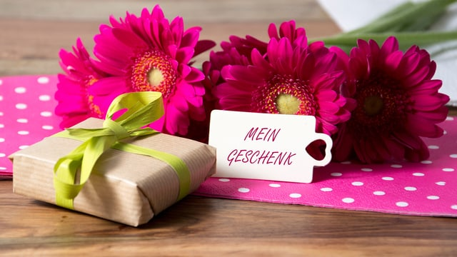 Ein Geschenk, eine Geschenkkarte und rote Astern auf einem Tisch.