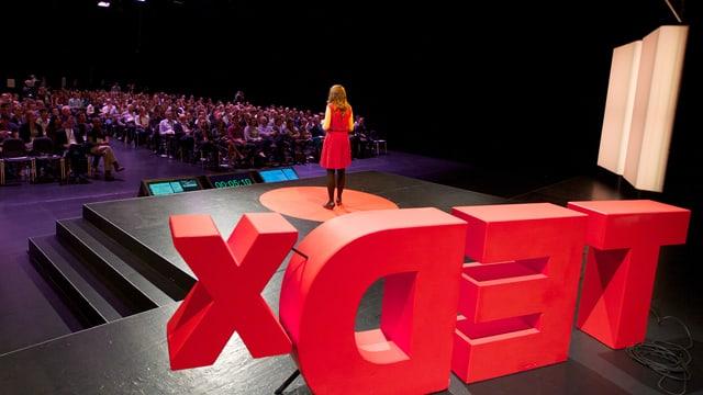 Eine Frau in rotem Kleid spricht vor sitzenden Menschen.