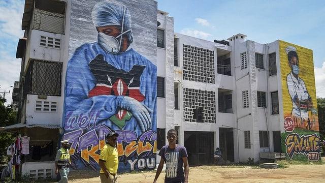 Afrikaner stehen vor einem Gebäude, auf dem zwei riesige Gemälde zu Ehren der Coronaarbeiter in Spitälern prangen.