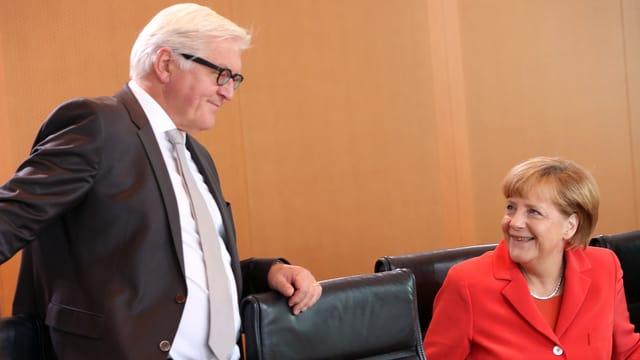 Steinmeier stehend und zur sitzenden Merkel hingewendet, die ihn anlächelt.